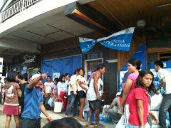 避難所で水やお米の配給を待つ人々の列